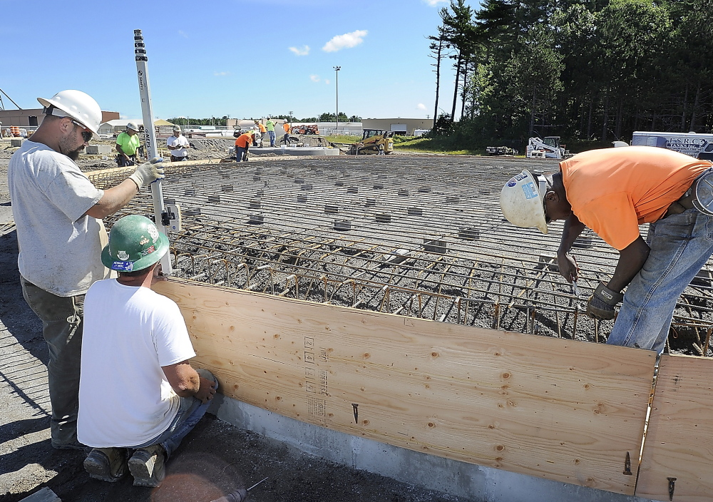 Chris Cormier, left, and Rick Podkowka build the concrete form as Bruce Ricks, right, installs the rebar that will be part of a garbage-eating power-generation plant  at Brunswick Landing.