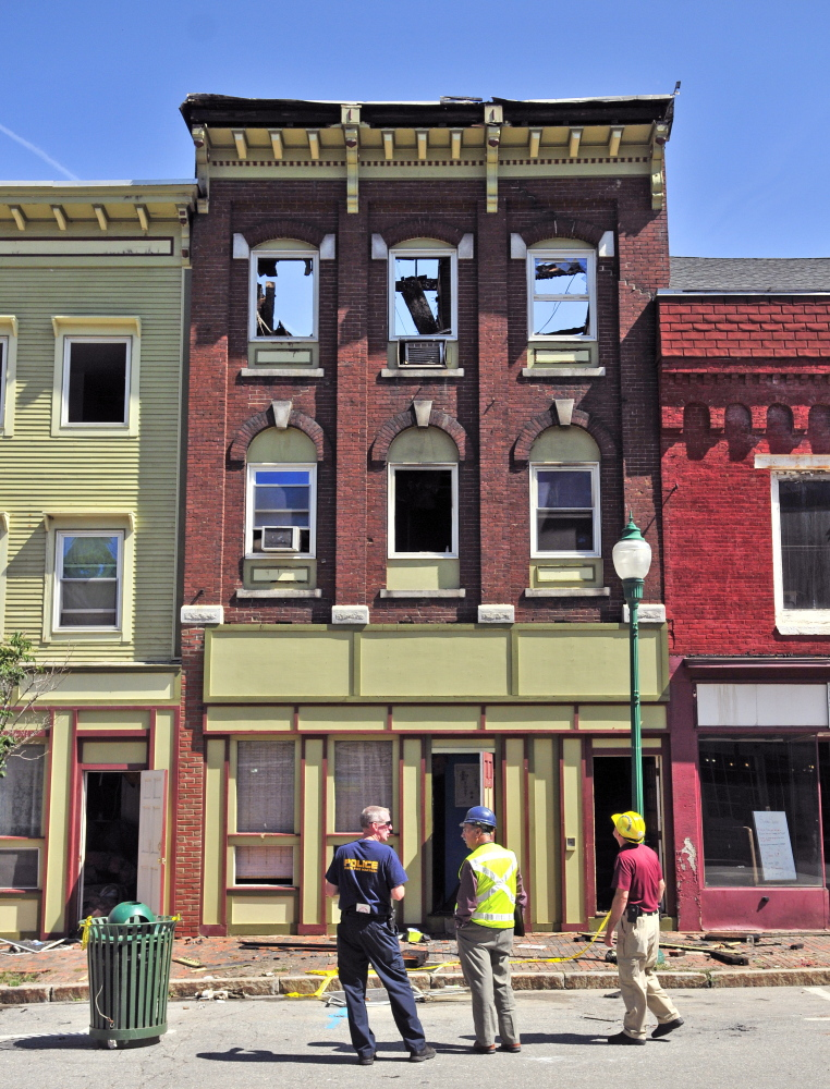 Officials stand in front of the scene the morning after a major fire ripped through downtown Gardiner, where officials hope a rebuilding effort can save the structures.