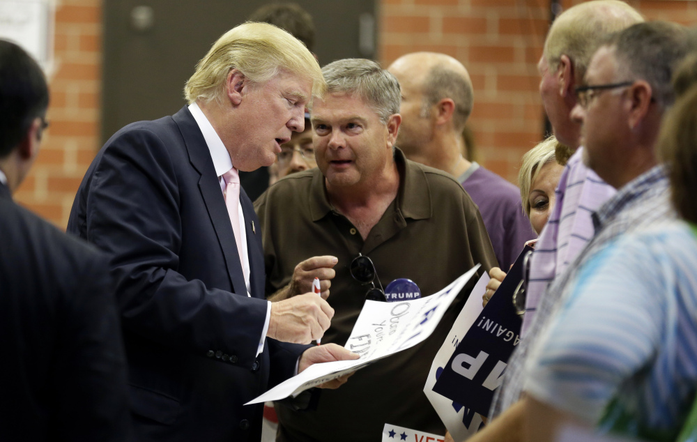 Republican presidential candidate Donald Trump signs autographs after speaking at a rally and picnic, Saturday in Oskaloosa, Iowa.