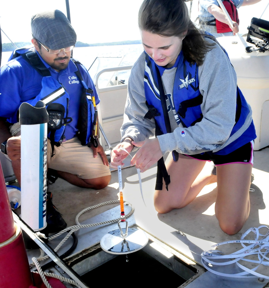 Colby College student Ellie Irish, right, lowers a Secchi disk that measures water clarity as fellow student Sergio Madrigal prepares other equipment to determine water quality on Great Pond in Belgrade on Thursday.