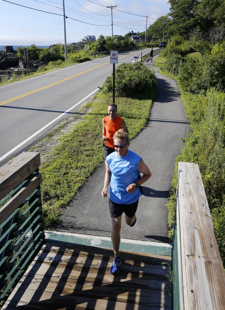 Al Swallow of South Portland, front, and Paul Letalien of Portland run along Shore Road in Cape Elizabeth while training for the 18th running of the TD Beach to Beacon 10K, which culminates farther up the road at Fort Williams Park.