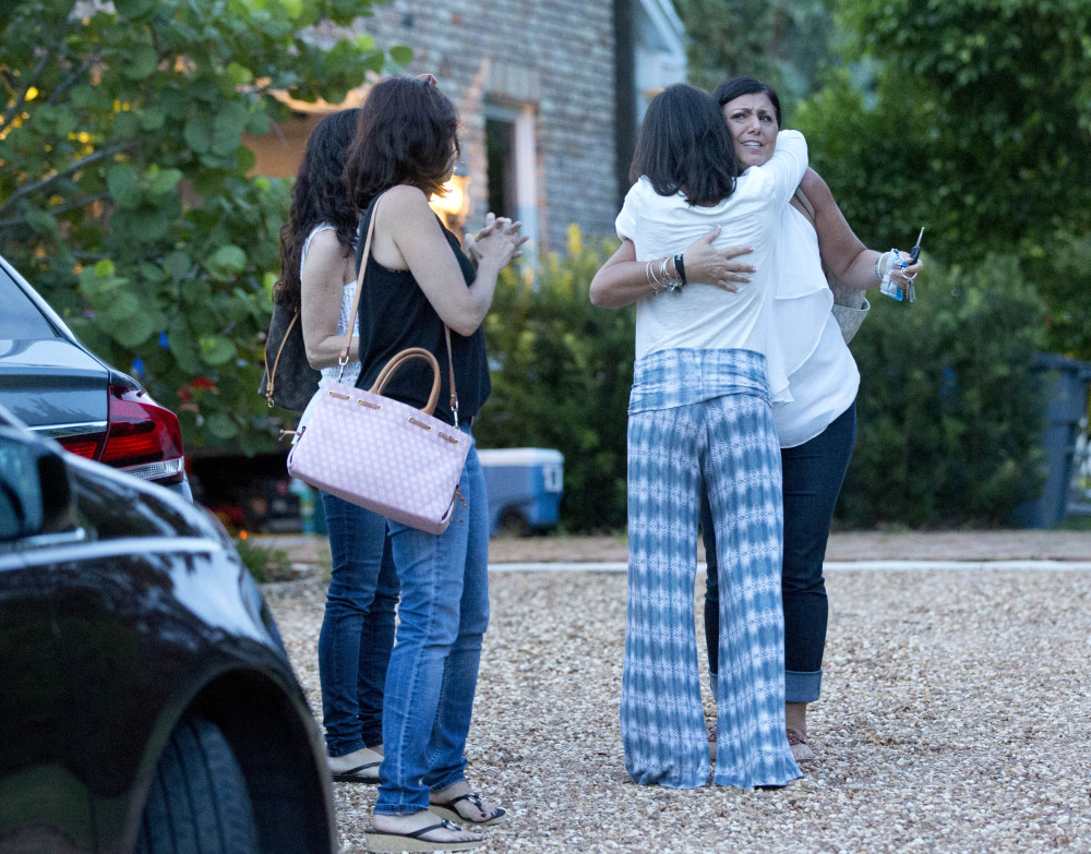 A group of people hug before leaving the house of one of the two missing 14-year-old fishermen, Sunday in Tequesta, Fla.