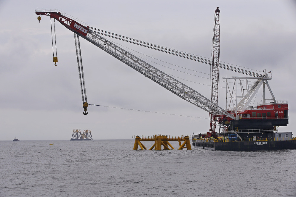 The first foundation jacket installed by Deepwater Wind in the nation's first offshore wind farm construction project is seen next to a construction crane Monday off Block Island, R.I.