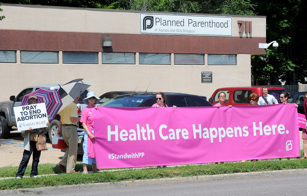 A man holding a sign stands next to five women holding a large banner supporting Planned Parenthood of Kansas and Mid-Missouri on Tuesday in front of Planned Parenthood in Columbia, Mo.  The Associated Press