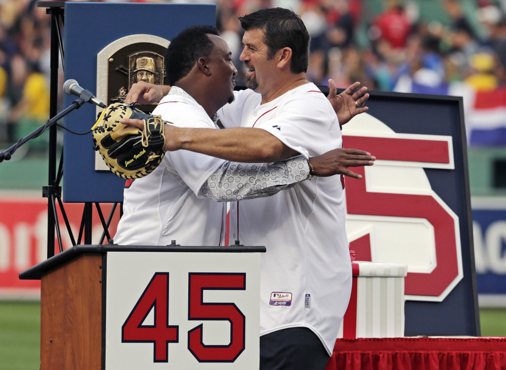 Baseball Hall of Fame member and former Boston Red Sox pitcher Pedro Martinez is embraced by former teammate Jason Varitek after his jersey was retired Tuesday at Fenway Park.