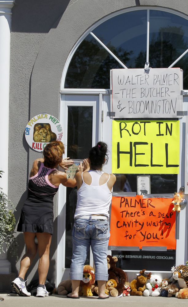 Women add signs to the door outside Dr. Walter James Palmer's dental office in Bloomington, Minn., on Wednesday. Palmer's killing of a protected lion just outside Hwange National Park in Zimbabwe had led to calls for an end to trophy hunting.