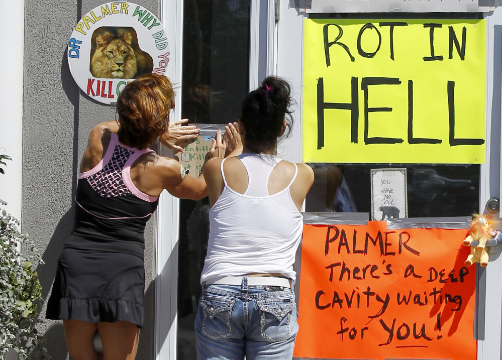 Two women post a sign outside Dr. Walter James Palmer's dental office in Bloomington, Minn., Wednesday.