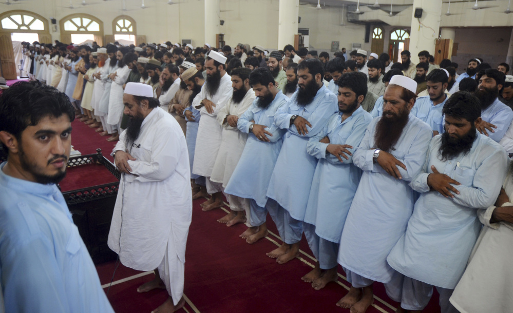 Hafiz Saeed, leader of Pakistan's religious group Jamaatud Dawa, front, leads a funeral prayers for Taliban leader Mullah Mohammad Omar at a mosque in Lahore, Pakistan, Thursday, July 30, 2015. Afghanistan's Taliban on Thursday confirmed the death of Mullah Omar, who led the group's self-styled Islamic emirate in the 1990s, sheltered al-Qaida through the 9/11 attacks and led a 14-year insurgency against U.S. and NATO troops. (AP Photo/Ahmed Ali)