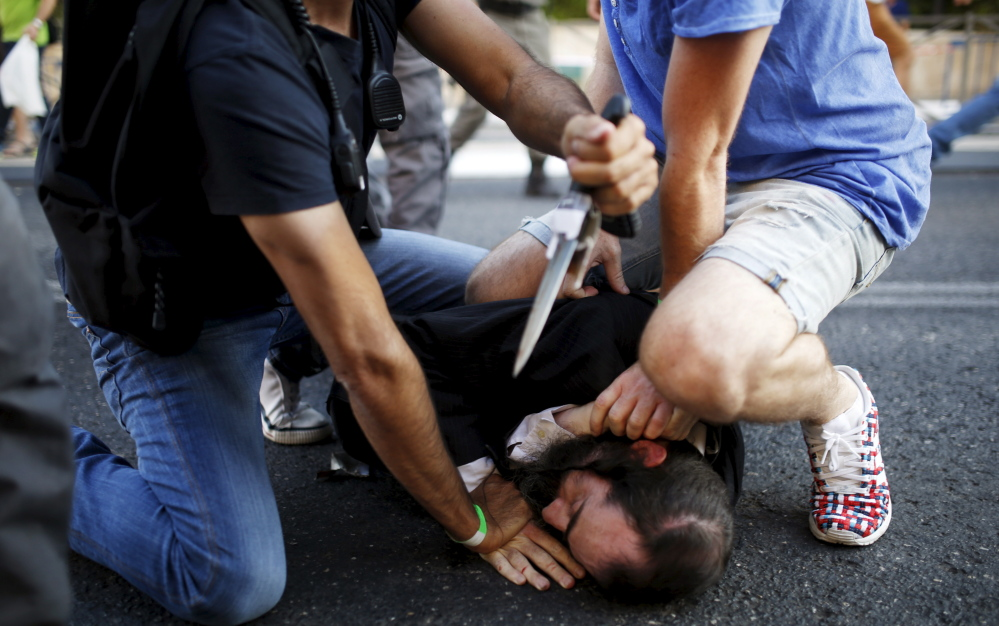 An assailant is subdued after he stabbed participants at Thursday's gay pride parade in Jerusalem. The attacker also had stabbed people at the parade in 2005, police say.