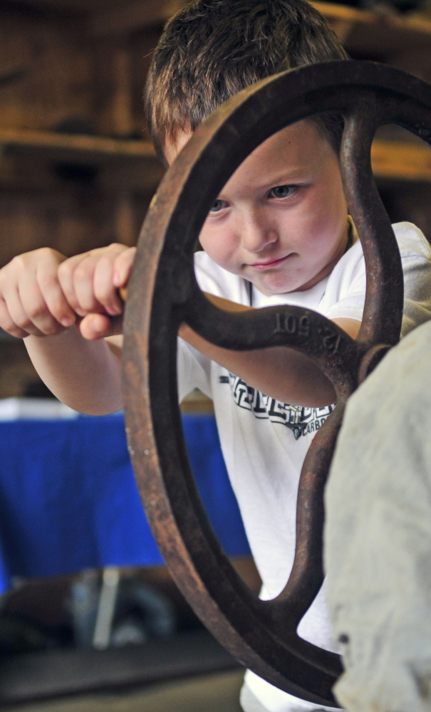 Alexander Sciolino turns the crank. His mother, Kristin Sciolino of Greene, is the daughter of Gary Buzzell and helps give demonstrations at the fair.