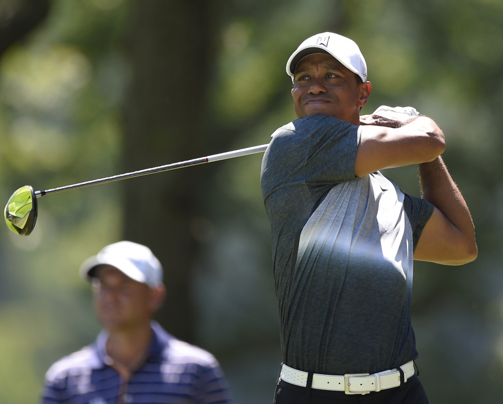 Tiger Woods watches his tee shot soar on the fifth hole of the Quicken Loans National on Friday, in the process of carding a 5-under 66 that left him tied for fifth, three shots behind Ryo Ishikawa.