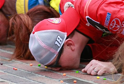 Kyle Busch kisses the bricks on the start/finish line after winning the NASCAR Brickyard 400 at Indianapolis Motor Speedway in Indianapolis on Sunday. The Associated Press