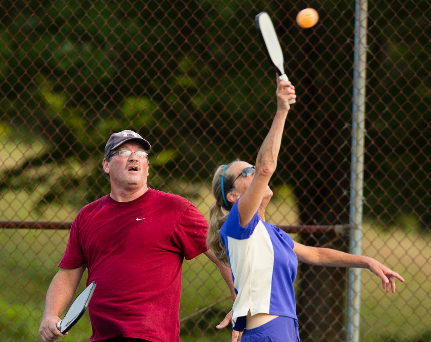 Carolee Carter of Falmouth returns a volley as teammate Dan Heckathorn of Gorham looks on while playing pickleball. Carl D. Walsh/Staff Photographer
