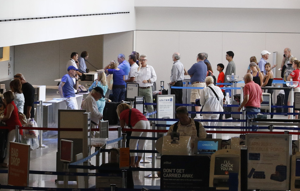 Travelers wait in line Saturday at the Portland International Jetport. Some flights were delayed or canceled due to