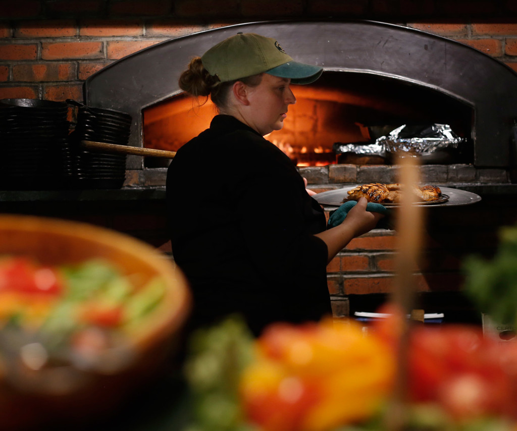 Beane, a banquet chef at Harraseeket Inn pulls food out of the pizza oven.