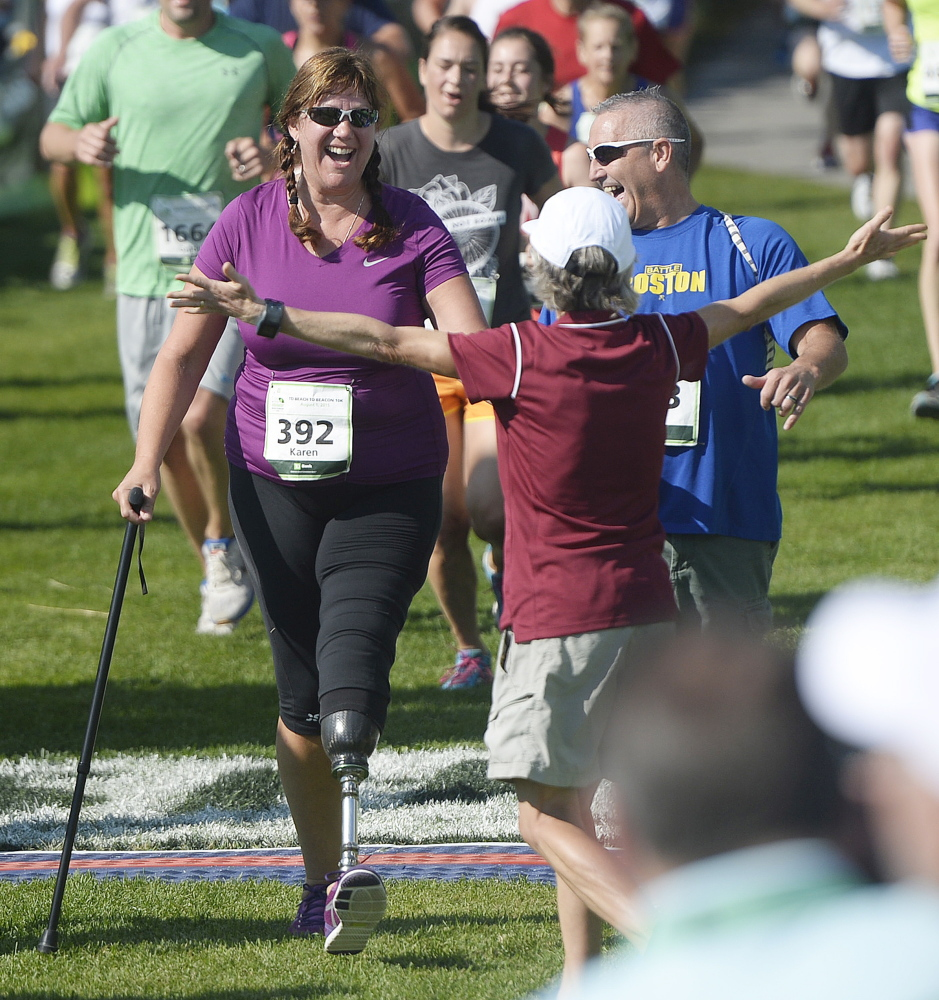 Karen Rand McWatters formerly of Westbrook, is greeted at the finish line by race founder Joan Benoit Samuelson after finishing the TD Beach to Beacon 10K Saturday. McWatters is a survivor of the 2013 Boston Marathon bombing, having lost the lower portion of her left leg.