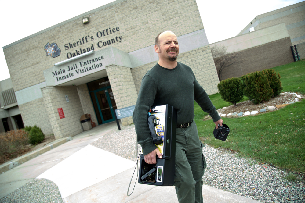 """Greg Andrick collects a pay phone from the jail in Pontiac, Mich. """"This used to be quite a booming business,"""" he said."""