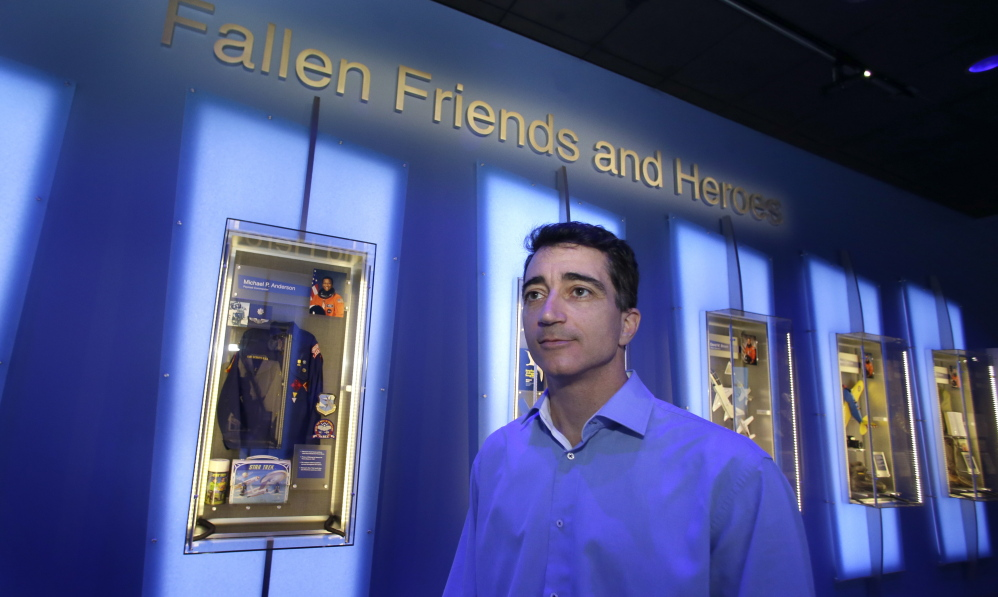 """Michael Ciannilli, who oversaw the """"Forever Remembered"""" exhibit and memorial to the astronauts who died on the Columbia and Challenger space shuttles, stands in the display at the Kennedy Space Center Visitor Complex in Cape Canaveral, Fla."""