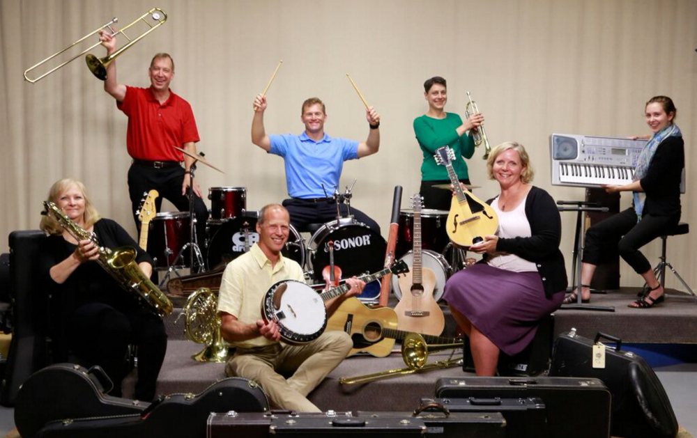 Members of the Maine Public Broadcasting Network staff show some of the musical instruments that were collected to be refurbished and distributed to needy young musicians.