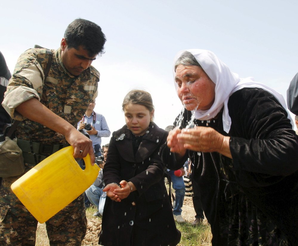 A member of the Kurdish Peshmerga helps out a woman and girl who were rescued from the Islamic State earlier this year near Kirkuk, Iraq. The U.N. says the Islamic State has been selling children like commodities.