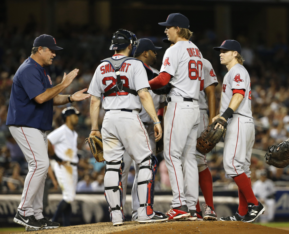Boston Red Sox manager John Farrell applauds starting pitcher Henry Owens (60) as he removes Owens from Tuesday night's game against the New York Yankees. Owens pitched into the sixth inning against New York in his major league debut.
