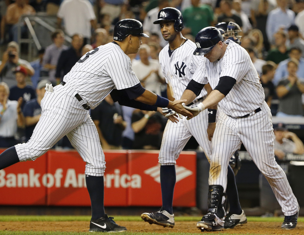 The Yankees' Alex Rodriguez, left, celebrates with Brian McCann after Rodriguez and Chris Young, center, scored on McCann's seventh-inning home run. Boston's bullpen was ineffective in a 13-3 loss.