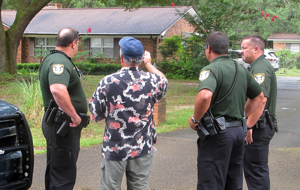 Escambia County Sheriff's deputies talk with an unidentified man Wednesday outside the Pensacola-area home where three family members were found dead on July 28.