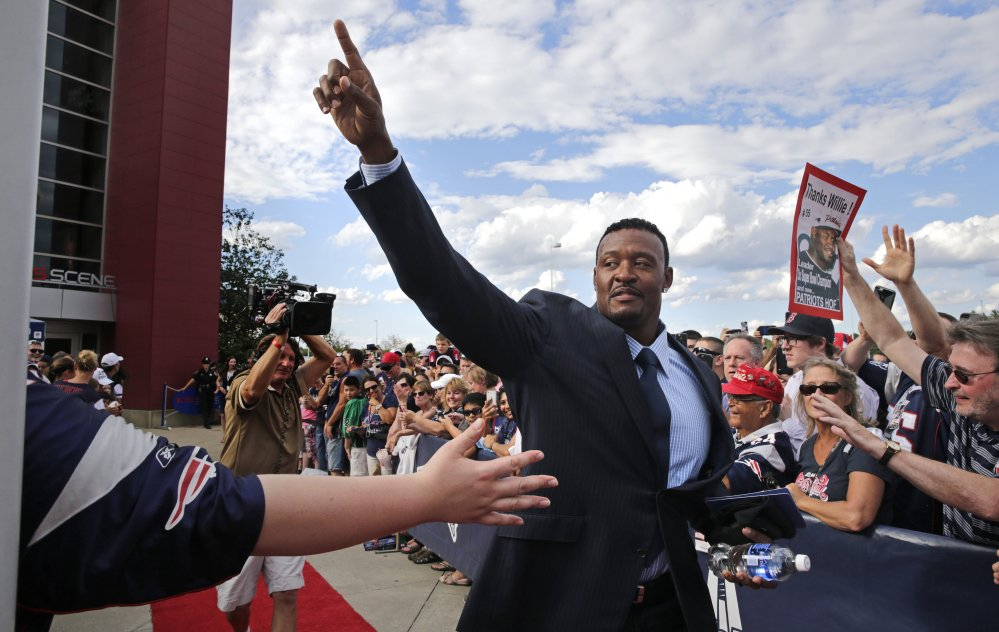 Former New England Patriots linebacker Willie McGinest acknowledges fans as he is introduced while being inducted into the Patriots Hall of Fame prior to a training session in Foxborough, Mass., on Wednesday.