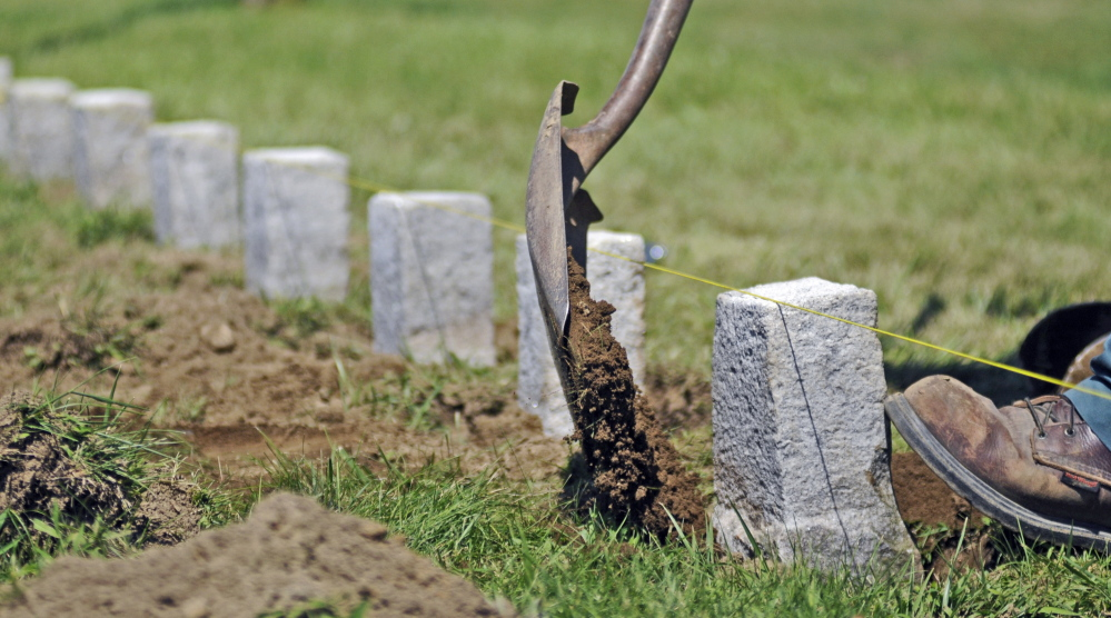 Kevin Miller straightens a row of 4-by-4-inch granite markers Wednesday in one of the soldiers' lots at Mount Pleasant Cemetery in Augusta.