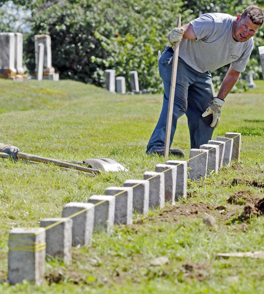 Kevin Miller checks the alignment of a row of granite markers Wednesday in one of the soldiers' lots at Mount Pleasant Cemetery in Augusta.