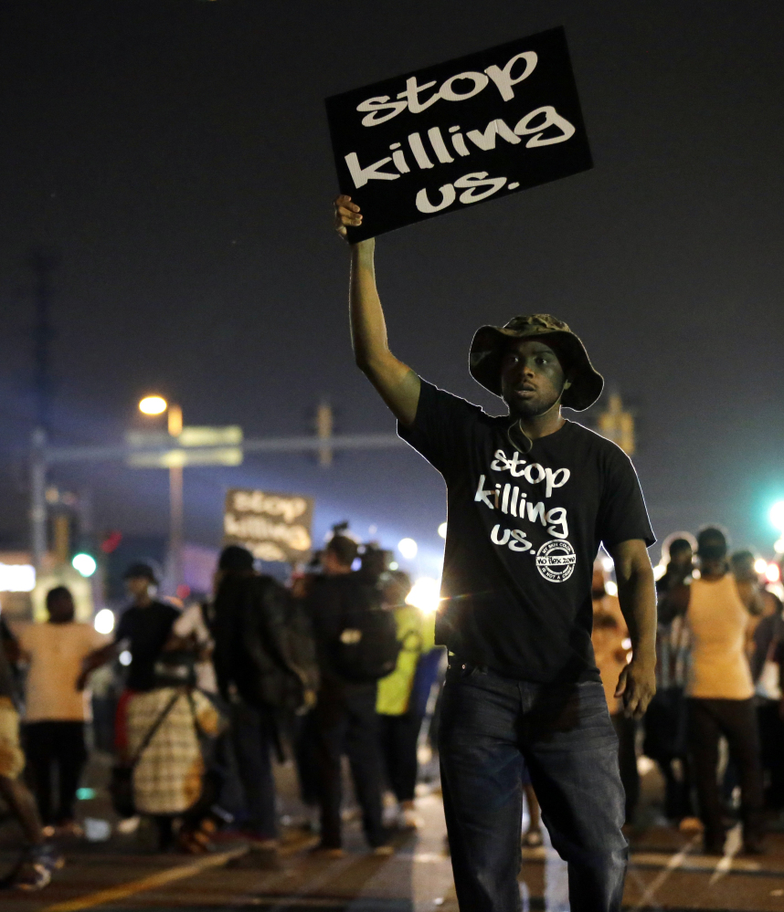 Protesters demonstrate in Ferguson, Mo., on Aug. 18, 2014. Recently released polls show that more white Americans believe blacks are treated less fairly than others by law enforcement officials.