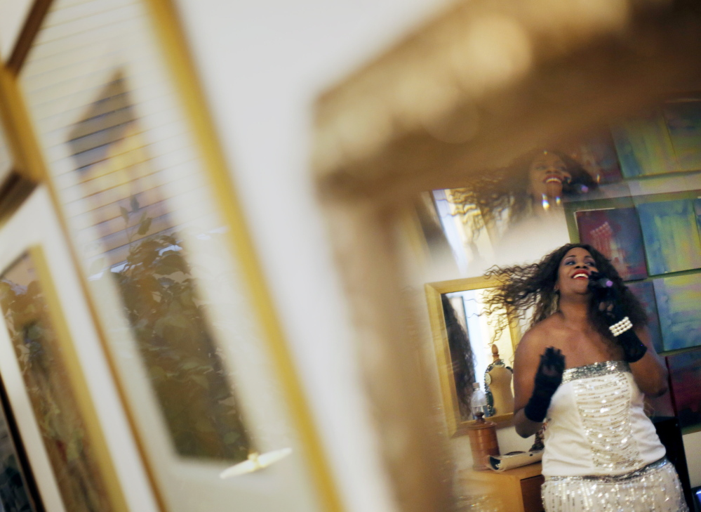 Local singer Venus LaBelle is reflected in a mirror while performing at a fundraiser for the Museum of African Art and Culture. Derek Davis/Staff Photographer