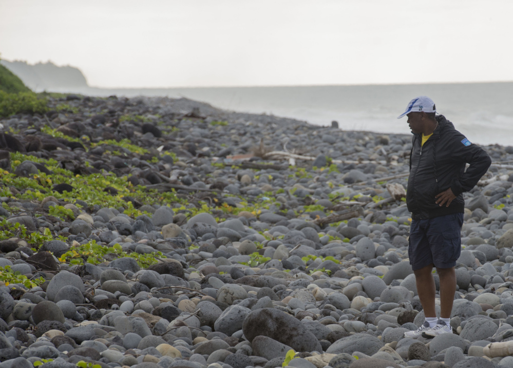 An unidentified man walks on Reunion's Saint-Andre beach, as the search for more debris from the missing Malaysian Airlines Flight 370 continues Thursday.