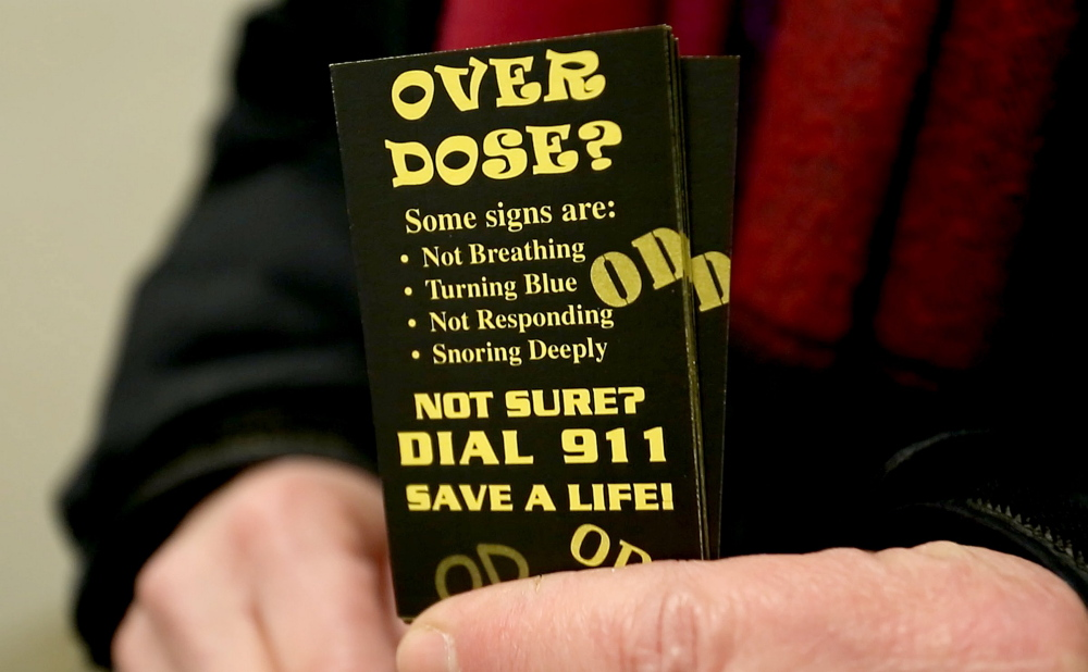 Ronni Katz of the city's Overdose Prevention Project holds cards she hands out urging people to call 911 if there is a suspected overdose. At least 14 people overdosed on opiates in one 24-hour period last weekend in Portland. In a typical 24-hour period, five or six overdoses of all types – including non-opiates – are reported.
