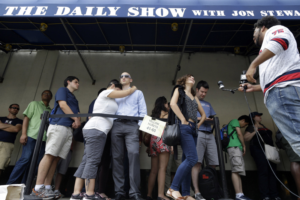 "Alexandra Mele, second from right, is interviewed and Ariana and Isaac Levin embrace as they wait in line to enter for the final taping of  ""The Daily Show with Jon Stewart"" on Thursday in New York. Stewart said goodbye Thursday after 16 years on the show that established him as America's foremost satirist of politicians and the media."