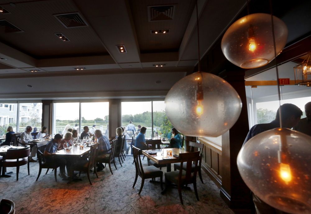 The dining room at Sea Glass overlooks Inn by the Sea's grounds and the ocean beyond.