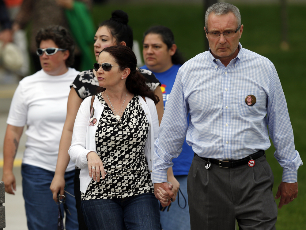 Tom Teves, right, and his wife, Caren, who lost their son, Alex, in the massacre in Aurora, Colo., in July 2012, leave the Arapahoe County Courthouse on Friday after jurors disagreed on whether James Holmes should get the death penalty.