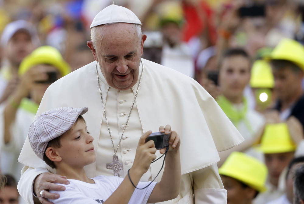 Pope Francis is shown his portrait taken by a boy as he arrives in St. Peter's Square at the Vatican for an audience with altar boys and girls Tuesday. The pontiff says children are damaged when their parents feel shunned by the church.