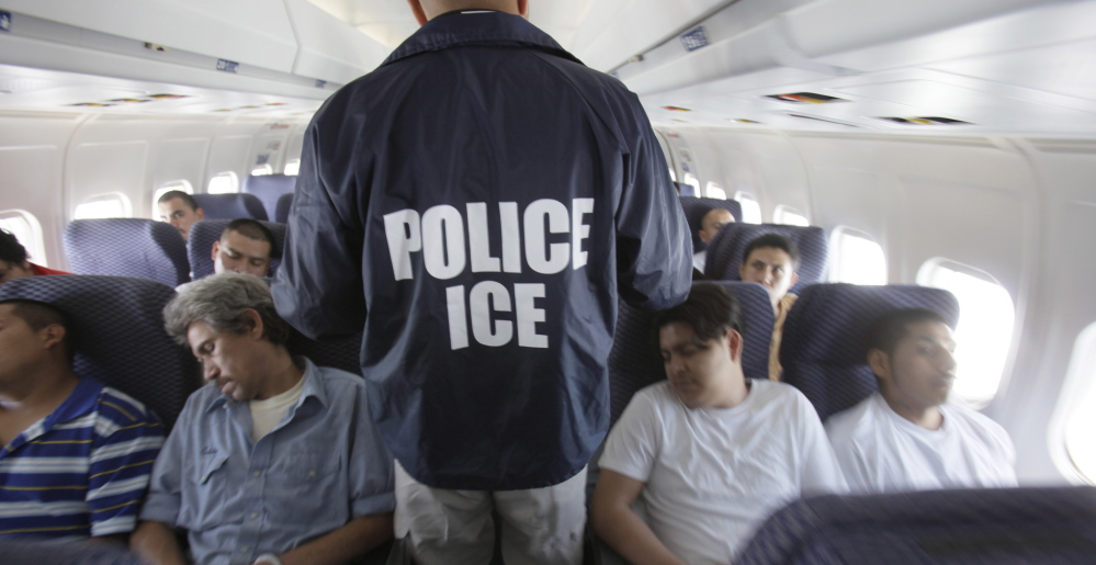 A federal Immigration and Customs Enforcement agent walks among shackled Mexican immigrants being deported in 2010.