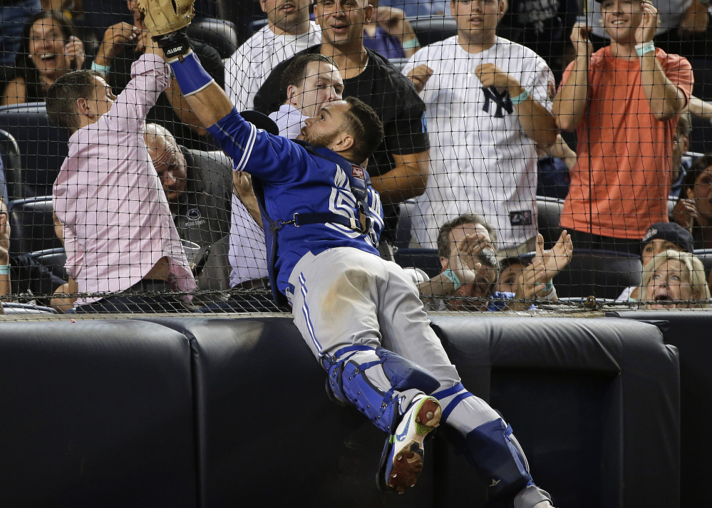 Blue Jays catcher Russell Martin catches a foul pop as he leaps against the backstop netting during the seventh inning of Toronto's 2-1, 10-inning victory over the Yankees at New York.