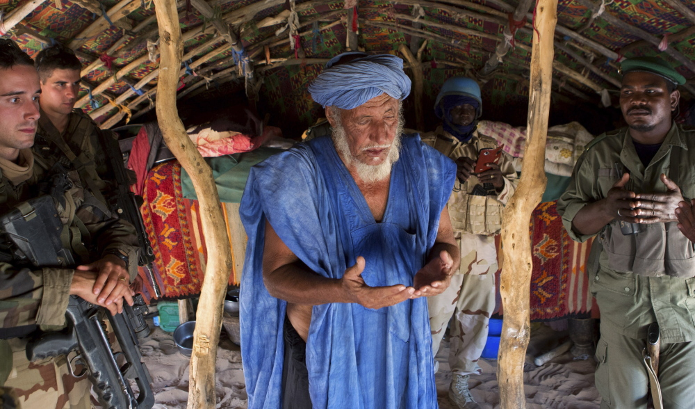 A village chief prays in 2014 after meeting with French soldiers north of Timbuktu, an area where Islamic extremists are now threatening the civilian population.