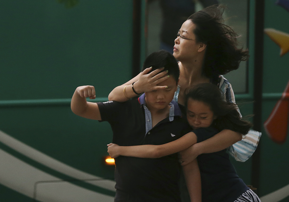 A mother holds her children as Typhoon Soudelor strikes Friday in Taipei, Taiwan. The storm left six dead there and was battering southeast China by late Saturday.