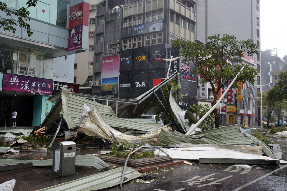 A street corner is filled with a mangled rooftop brought down by strong winds from Typhoon Soudelor in Taipei, Taiwan, Saturday. Soudelor's wind speeds topped 100 mph, with gusts over 120 mph, according to Taiwan's Central Weather Bureau.