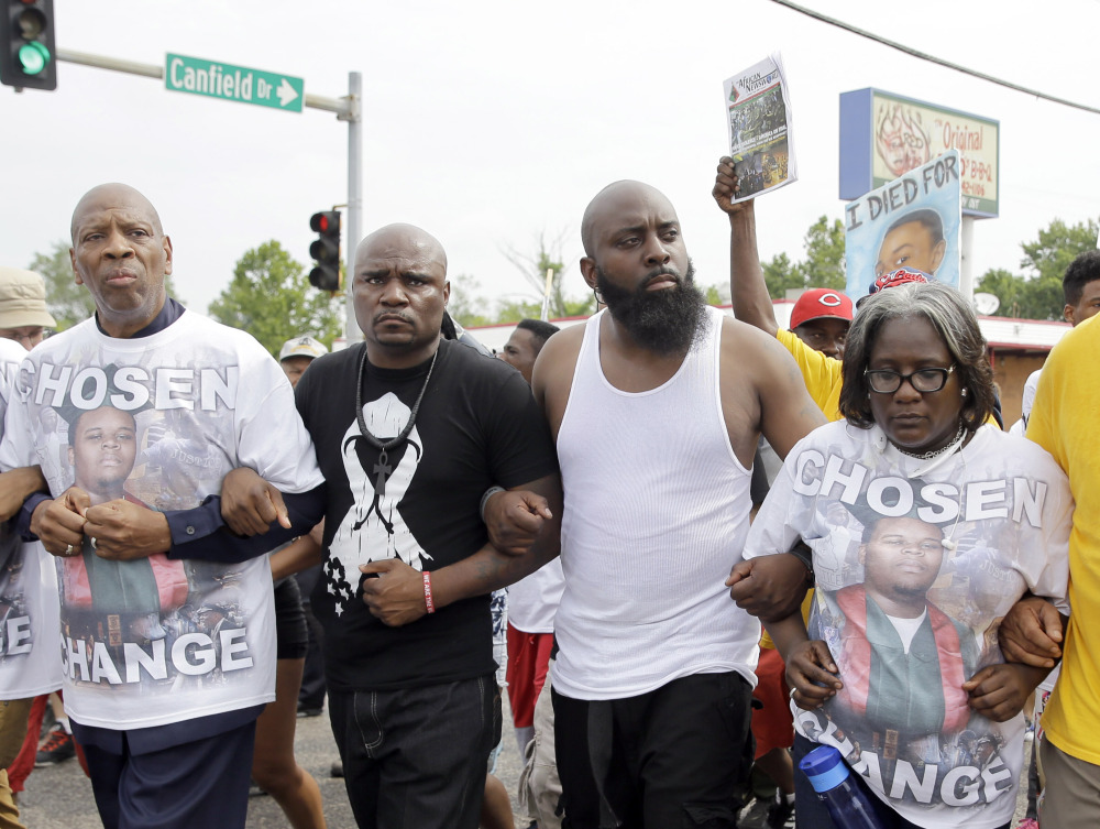 Michael Brown Sr., in a white tank top, locks arms with others as he takes part in a parade in memory of his son, Michael Brown, Saturday, in Ferguson, Mo., where several events are marking the one-year anniversary of the fatal shooting.