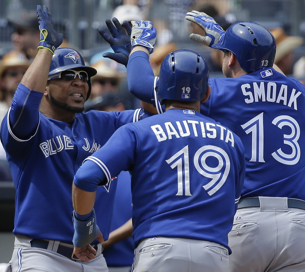 Toronto's Edwin Encarnacion, left, greets Jose Bautista and Justin Smoak after Smoak hit a grand slam during a 6-0 win over the Yankees in New York.