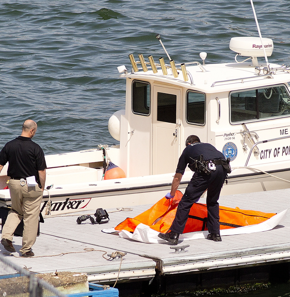 Portland police tend to a body that was recovered Monday from Portland Harbor near the Ocean Gateway terminal.