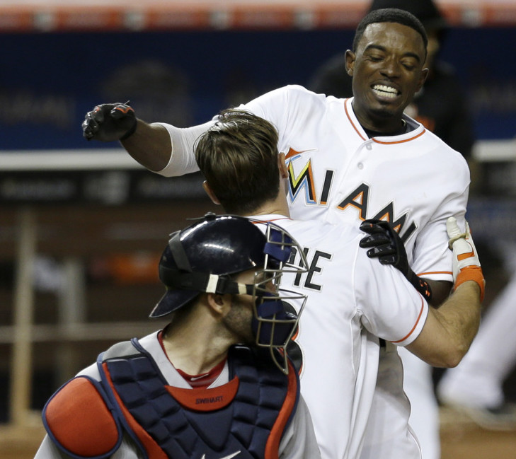The Marlins' Dee Gordon is lifted by teammate Cole Gillespie after scoring the game-winning run on a base hit by Justin Bour in the 10th inning Tuesday night in Miami. The Marlins won 5-4.