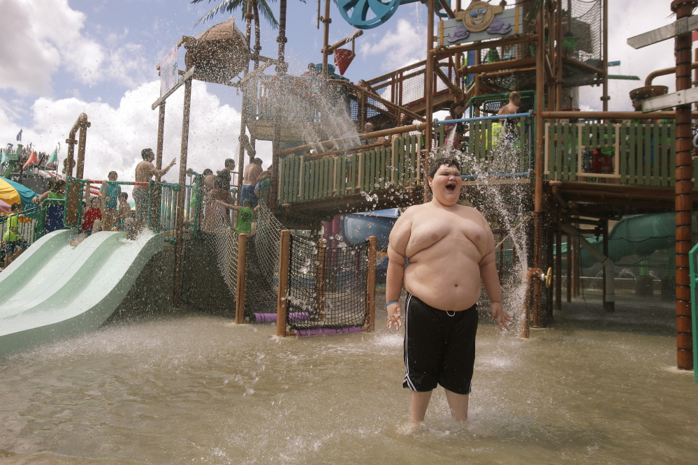 Dylan Dean, 11, smiles after being doused with water at Pirates Paradise at Splashtown in Saco on Wednesday. The Saco amusement park flew Dylan, who has Asperger's syndrome and a condition that causes him to gain weight, and his family to Maine and gave them free passes to the park after they experienced an alleged bullying incident at a water park in their home state of Texas.