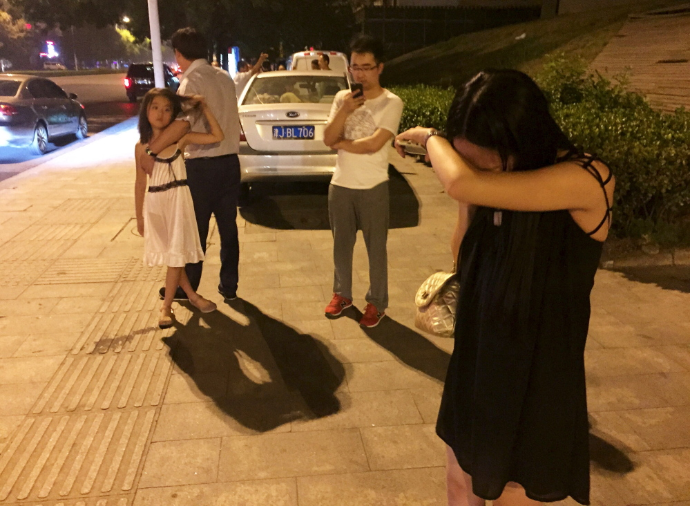 People react after a blast at Binhai new district, in Tianjin municipality, China, late Wednesday. The blast wave was felt several miles away, domestic media reported.