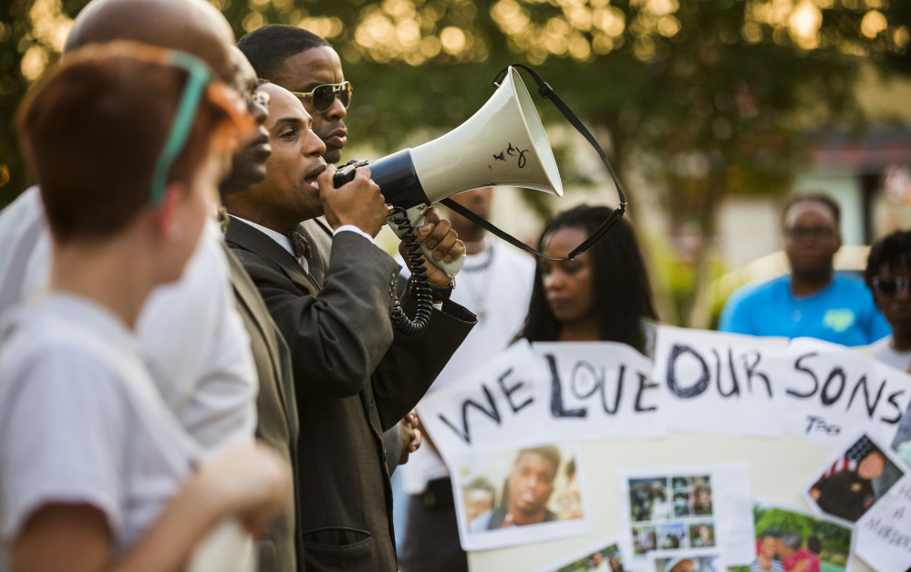 Lee Muhammad of the Nation of Islam speaks Tuesday outside the Arlington Police Department in Arlington, Texas, demanding that officer Brad Miller be charged in the death of Christian Taylor, an unarmed black 19-year-old, during a suspected burglary.